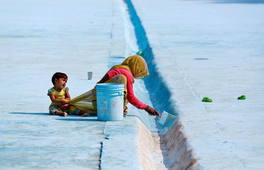 کودک توجه مادر خود را از کار در دهلی نو، هند منحرف مینماید